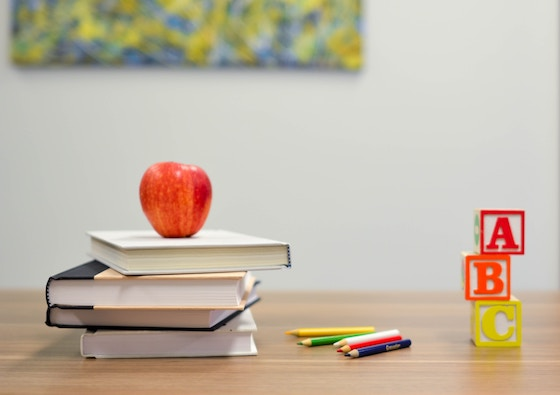 Books on a desk with an apple.