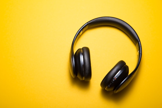 black headphones against yellow background.