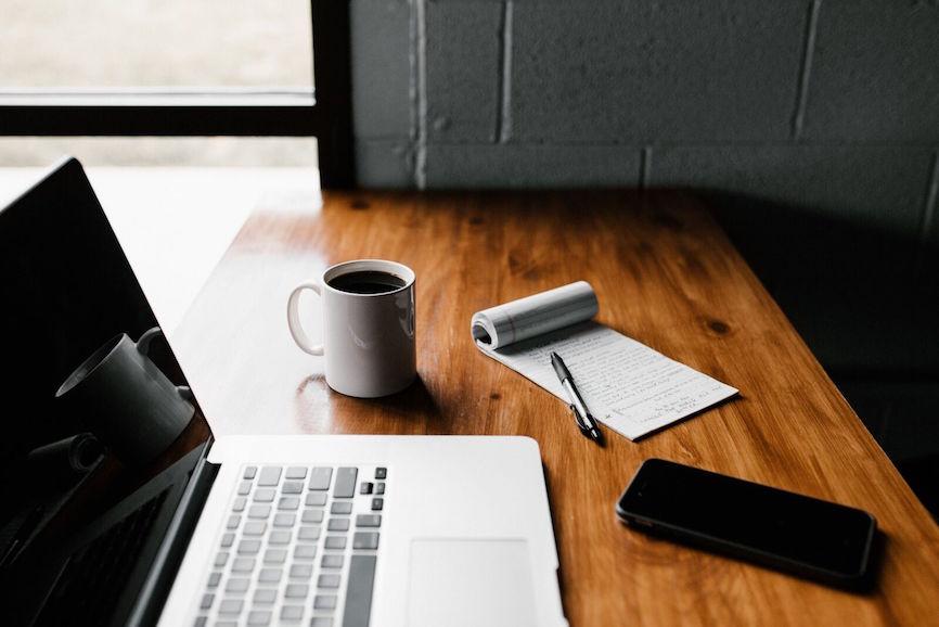 Membership pricing notepad beside laptop
