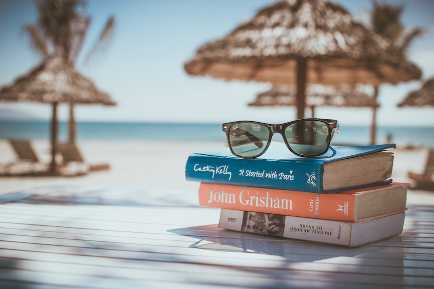 Books on the beach with glasses.