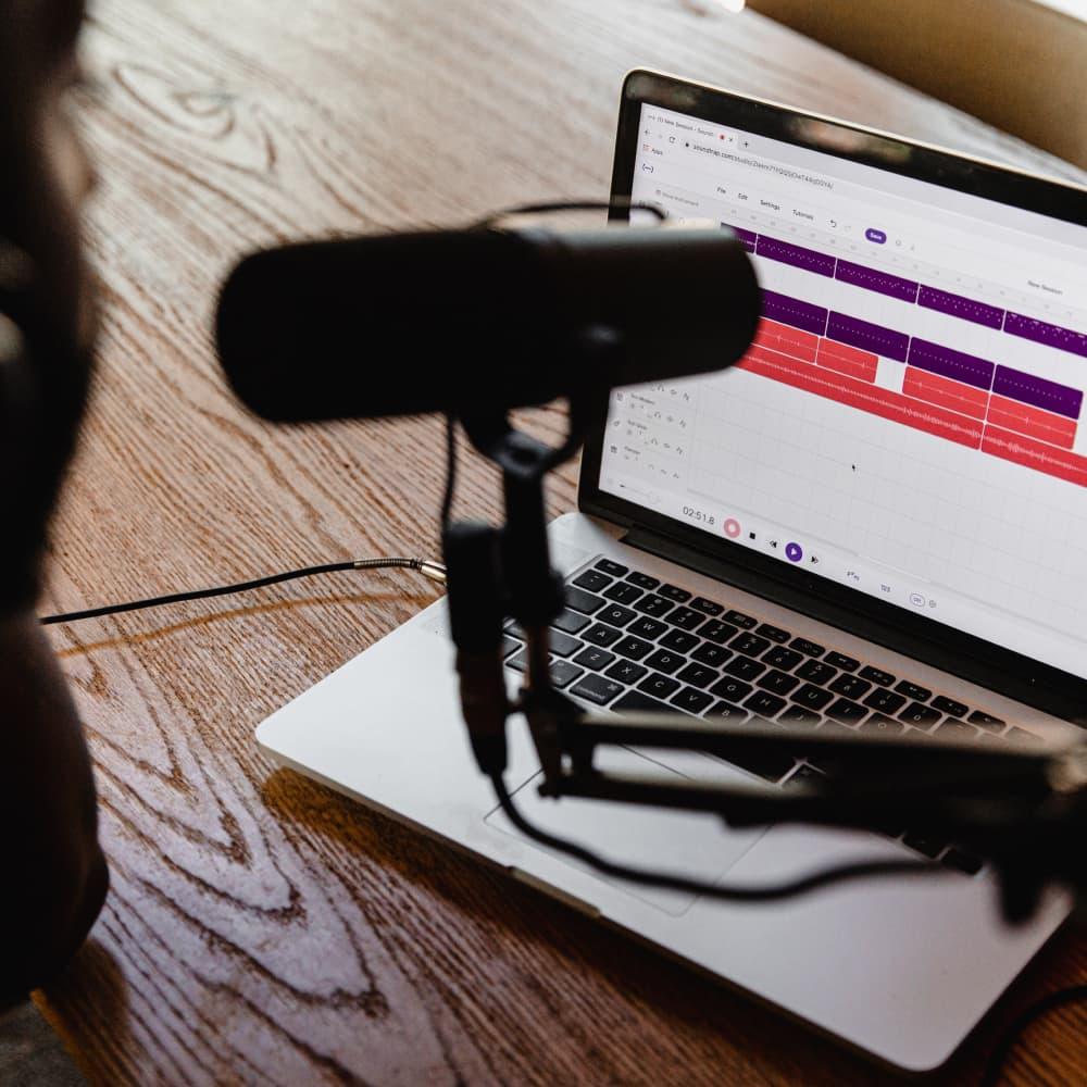 Podcast microphone with computer on wooden desk.